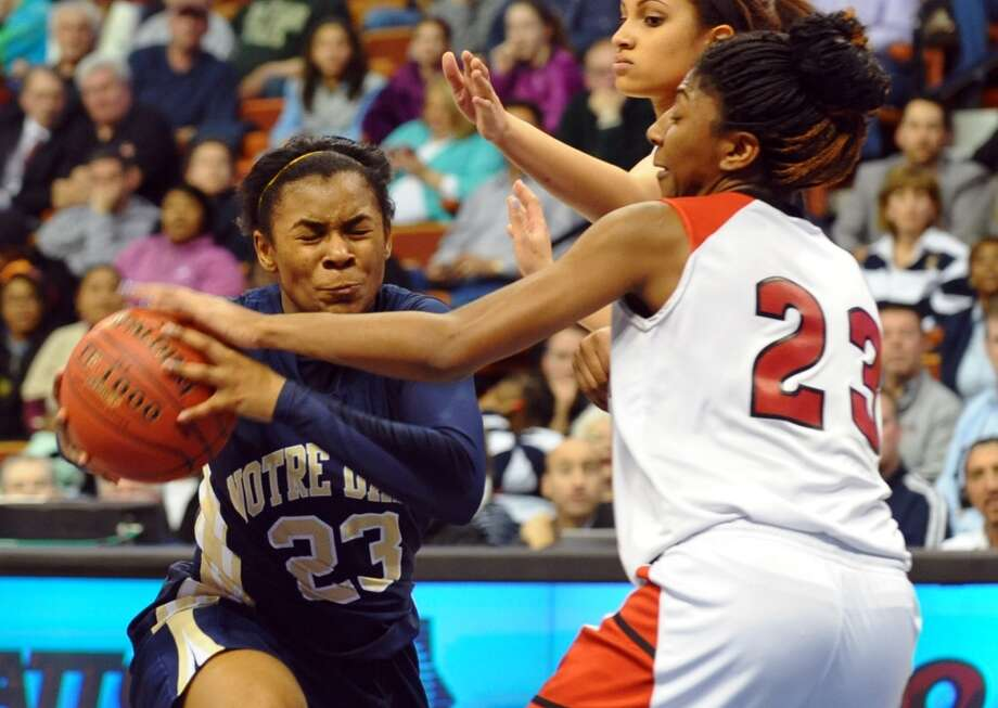 Notre Dame of Fairfield #23 Jovan Kingwood works to get the ball past Cromwell's #23 Janelle Harrison, during Class M girls basketball final action at the Mohegan Sun Arena in Uncasville, Conn. on Friday March 15, 2013.