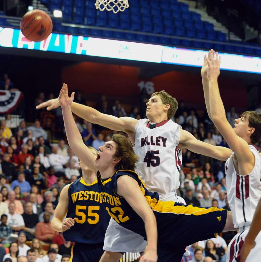 Weston's #42 Grant Limone misses a lay up attempt as he is pressured by Valey Regional's #45 Chris Polo, during Class M boys basketball final action at the Mohegan Sun Arena in Uncasville, Conn. on Friday March 15, 2013.