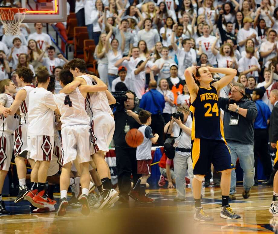 As Valley Regional celebrates their win, Weston's #24 Charlie DiPasquale walks of the court in Class M boys basketball final action at the Mohegan Sun Arena in Uncasville, Conn. on Friday March 15, 2013.