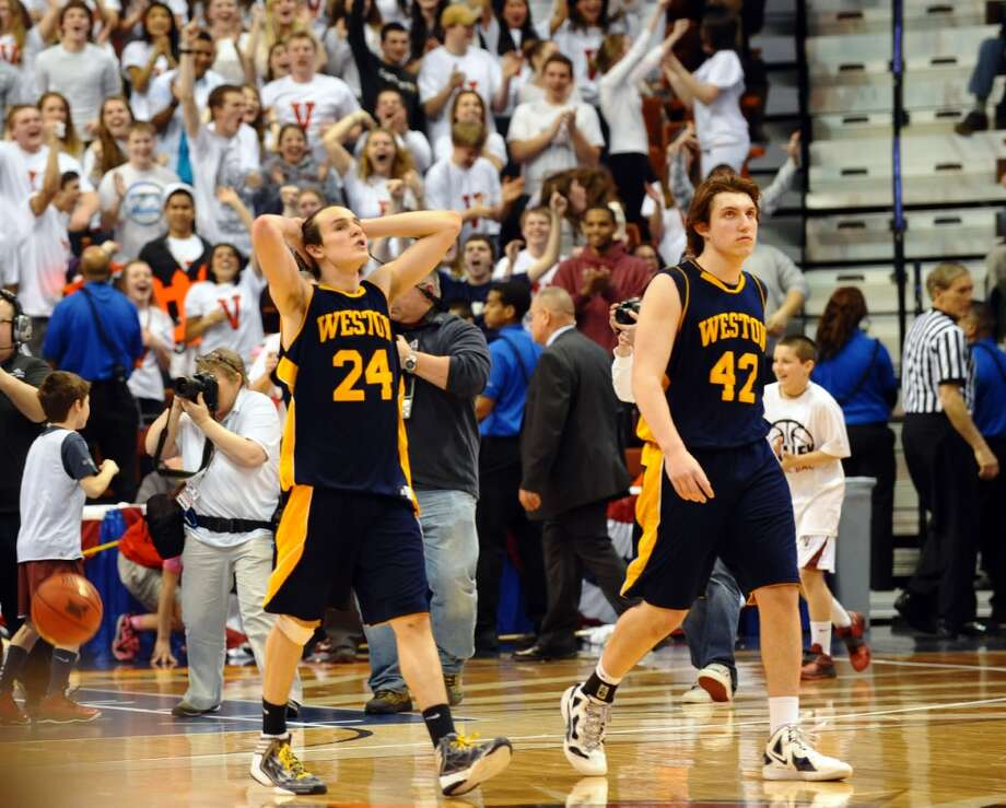 Weston's #24 Charlie DiPasquale, left, and #42 Grant Limone walk off the court after the the team was beat by Valley Regonal in Class M boys basketball final action at the Mohegan Sun Arena in Uncasville, Conn. on Friday March 15, 2013.