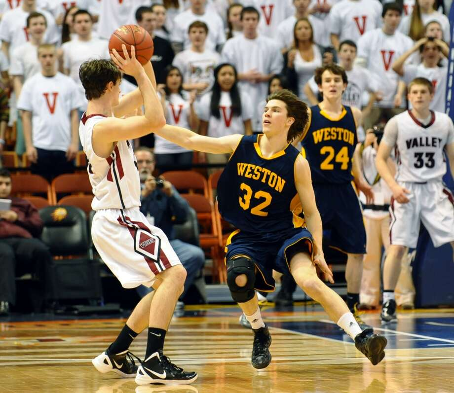 Weston's #32 Troy Flynn looks to slow down Valley Regional's #43 Chris Connor, during Class M boys basketball final action at the Mohegan Sun Arena in Uncasville, Conn. on Friday March 15, 2013.