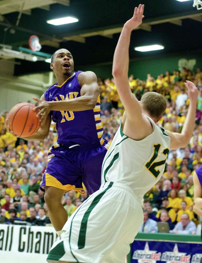 Albany's Mike Black, left, tries to shoot over Vermont's Sandro Carissimo during an NCAA college basketball game in the championship of the America East Conference tournament in Burlington, Vt. on Saturday, March 16, 2013. Photo: Glenn Russell, Glenn Russell /  AP Photo/The Burlington Free Press / The Burlington Free Press