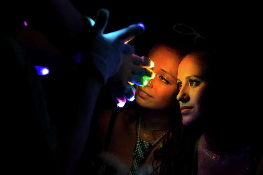 Girls enjoy a light show by a LED-gloved attendee at Lucky 2013. Photo: JORDAN STEAD / SEATTLEPI.COM