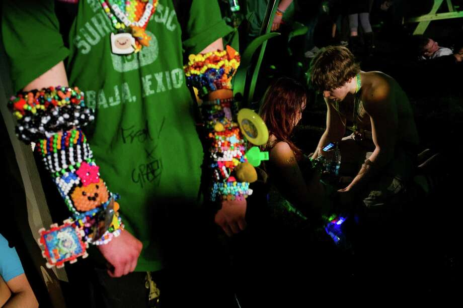 """A couple chats while an attendee laden with """"kandy"""" stands nearby at Lucky 2013. Photo: JORDAN STEAD / SEATTLEPI.COM"""