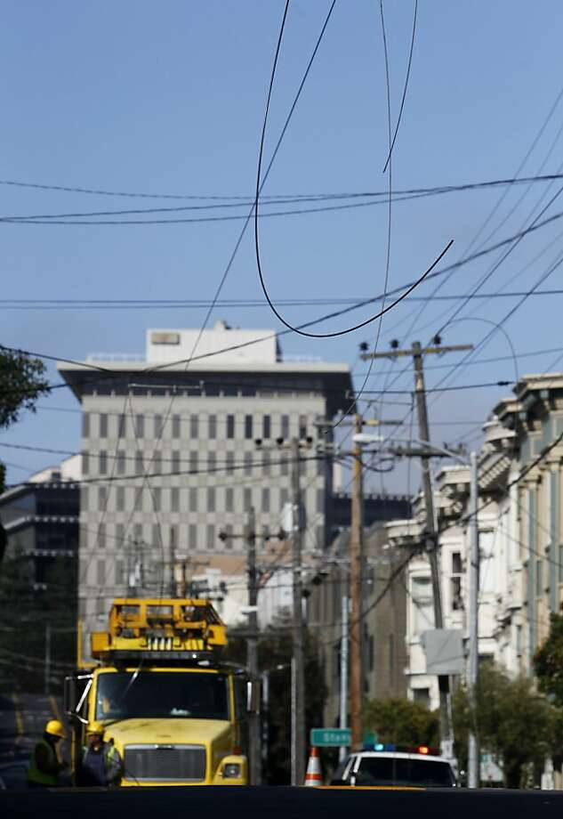 Muni power lines dangle above Parnassus Avenue at Shrader Street in San Francisco, Calif., after a PG&E line reportedly arced and came down, knocking out power to the neighborhood and disrupting service on the 6-Parnassus and 43-Masonic Muni bus routes on Saturday, March 16, 2013. Photo: Paul Chinn, The Chronicle