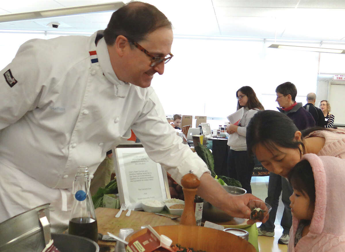 Jonathan Mathias, chef of A Dash of Salt, hands a sample of salad to Sharon Huynh and her daughter Kayla at the Food for Thought Expo on Saturday. FAIRFIELD CITIZEN, CT 3/16/13