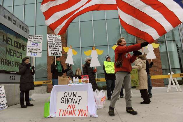 Charlie Samuels, right, of Saratogians for Gun Safety waves a U.S. flag outside in protest during the Arms Fair on Saturday, March 16, 2013, at the City Center in Saratoga Springs, N.Y. The New Eastcoast Arms Collectors Associates sponsored the event. (Cindy Schultz / Times Union) Photo: Cindy Schultz / 00021578A