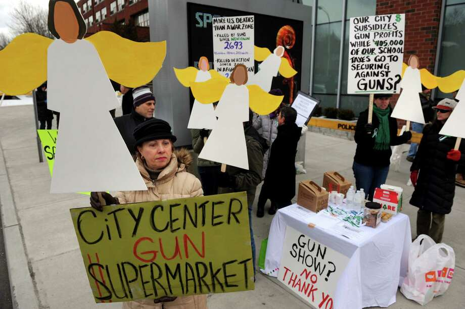 Mary-Sue D'Orazio, left, of Saratogians for Gun Safety joins other members outside in protest during the Arms Fair on Saturday, March 16, 2013, at the City Center in Saratoga Springs, N.Y. The New Eastcoast Arms Collectors Associates sponsored the event. (Cindy Schultz / Times Union) Photo: Cindy Schultz / 00021578A