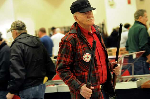 Robert Jensen of West Chazy, Clinton County, carries guns he has for sale during the Arms Fair on Saturday, March 16, 2013, at the City Center in Saratoga Springs, N.Y. The New Eastcoast Arms Collectors Associates sponsored the event. (Cindy Schultz / Times Union) Photo: Cindy Schultz / 00021578A