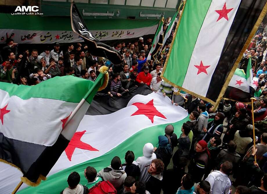 Protesters wave revolutionary flags on the second anniversary of the uprising in Aleppo, Syria. Photo: Hoep, Associated Press