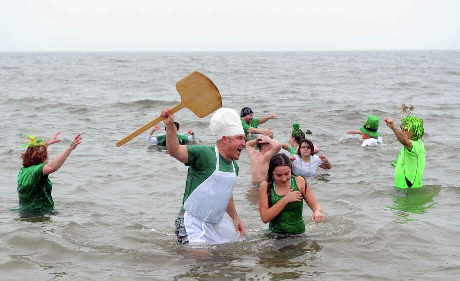 Robert Ludwig, of Milford, and his daughter Cristina, 11, run out of the water during the annual Leprechaun Leap to benefit the Literacy Center of Milford Saturday, Mar. 16, 2013 at Walnut Beach in Milford, Conn. Photo: Autumn Driscoll / Connecticut Post