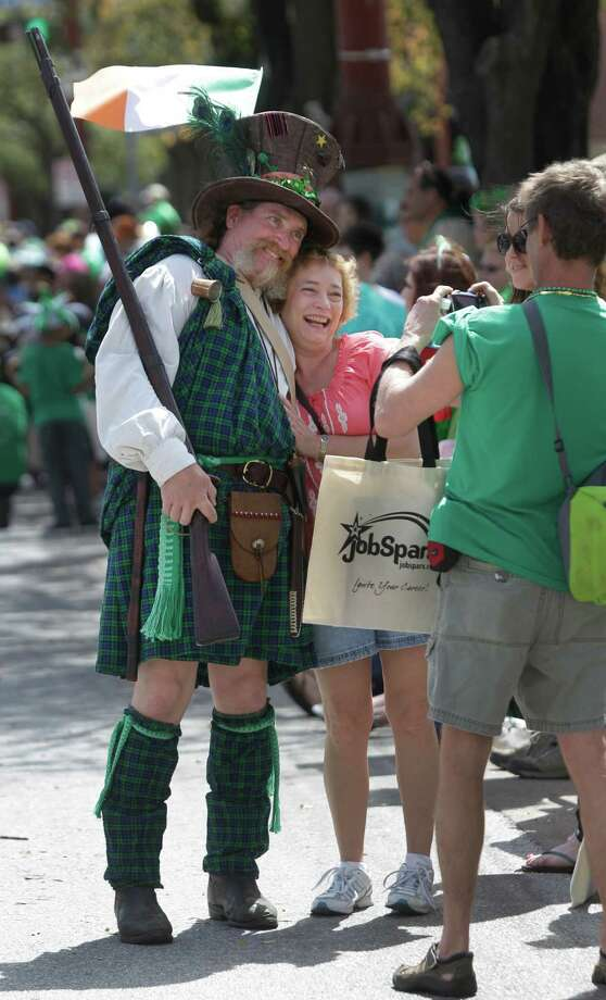 Texas Army member Pat Cumiskey, left, of Sweeny stops to have a photo with Mary Johnson taken by Brad Johnson, right, during the 54th annual Houston St. Patrick's Day Parade Saturday, March 16, 2013, in Houston. Photo: Melissa Phillip, Houston Chronicle / © 2013  Houston Chronicle