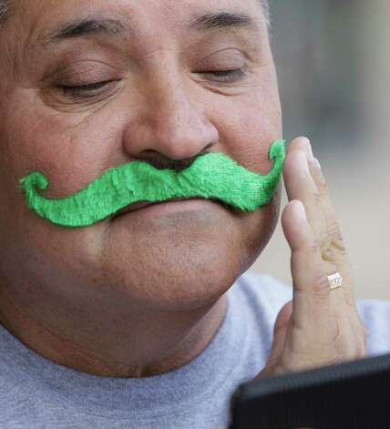 Luis Vega Sr. uses his cell phone as a mirror as he applies a green mustache during the 54th annual Houston St. Patrick's Day Parade Saturday, March 16, 2013, in Houston. Photo: Melissa Phillip, Houston Chronicle / © 2013  Houston Chronicle