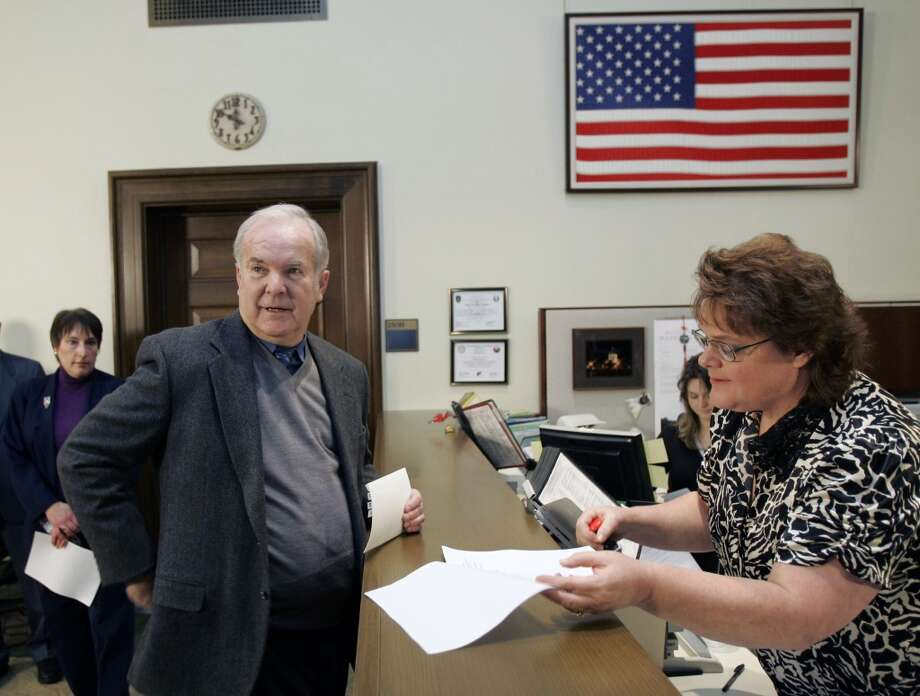 Former Washington Gov. Booth Gardner files an initiative with Teresa Glidden, right, of the state's Department of Elections to put the issue of legal assisted suicide on the ballot before voters in 2008 at the Capitol in Olympia.