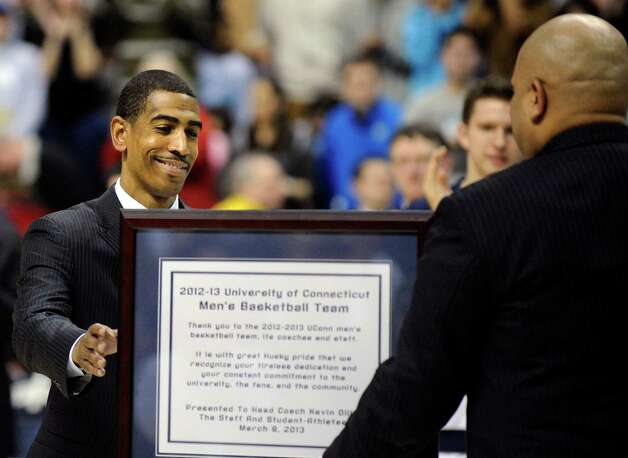 Connecticut coach Kevin Ollie, left, is presented a plaque by athletic director Warde Manuel after his team's 63-59 overtime win against Providence in an NCAA college basketball game in Storrs, Conn., Saturday, March 9, 2013. (AP Photo/Fred Beckham) Photo: Fred Beckham, Associated Press / FR153656 AP