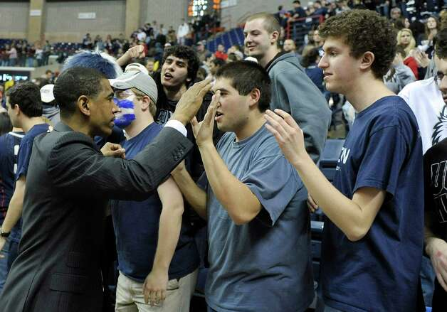 Connecticut coach Kevin Ollie, left, celebrates with fans after his team's 63-59 overtime win against Providence in an NCAA college basketball game in Storrs, Conn., Saturday, March 9, 2013. (AP Photo/Fred Beckham) Photo: Fred Beckham, Associated Press / FR153656 AP