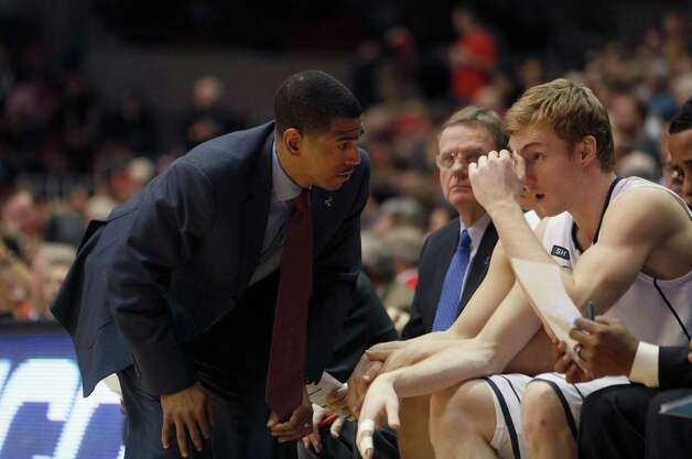 Connecticut head coach Kevin Ollie, left, talks with Connecticut forward Niels Giffey, right, during an NCAA college basketball game against Cincinnati, Saturday, March 2, 2013, in Cincinnati. Cincinnati won 61-56. (AP Photo/David Kohl) Photo: David Kohl, Associated Press / FR51830 AP