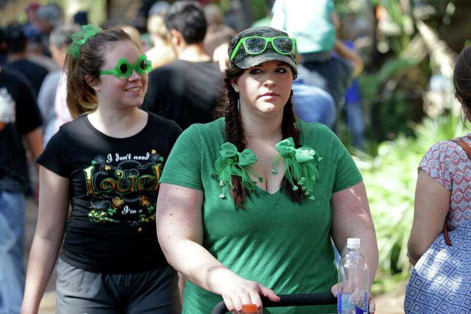 Angela Rios puts a shamrock hat decoration on her daughter Alexzandrea while Carlos Rodriguez watches as St. Patrick's Day is celebrated on the Riverwalk and La Villita  on  March 16, 2013. Photo: TOM REEL