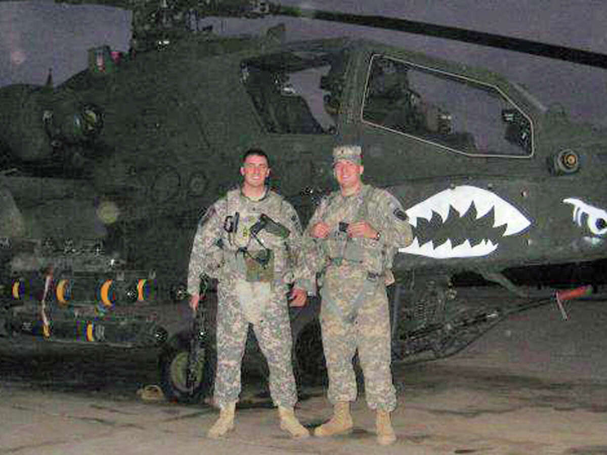 Daniel and Tyler Merritt in front of an Apache attack helicopter in Iraq on Thanksgiving Day in 2008. The two brothers have established a clothing line and a foundation to support wounded veterans.