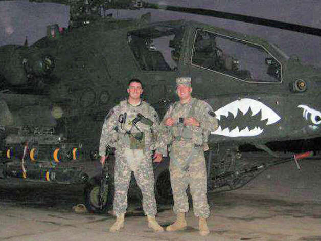 Daniel and Tyler Merritt in front of an Apache attack helicopter in Iraq on Thanksgiving Day in 2008. The two brothers have established a clothing line and a foundation to support wounded veterans. Photo: Contributed Photo
