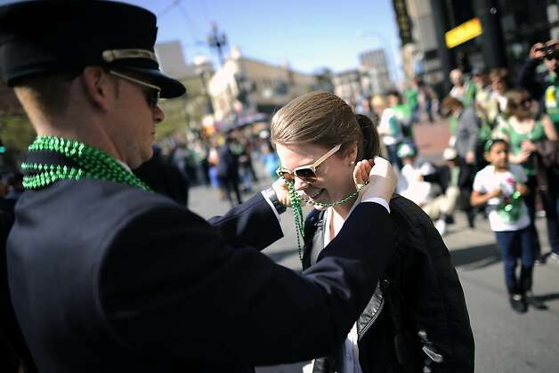 Visiting from Norway, Narah Bjellum receives a set of beads from a SF Firefighter during the annual St. Patrick's Day Parade in San Francisco, Saturday March 16th, 2013. Photo: Michael Short, Special To The Chronicle