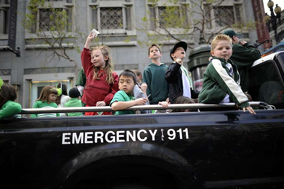 Children of police officers are seen in the back of a police truck as they throw candy and beads to the crowds at the annual St. Patrick's Day Parade in San Francisco, Saturday March 16th, 2013. Photo: Michael Short, Special To The Chronicle