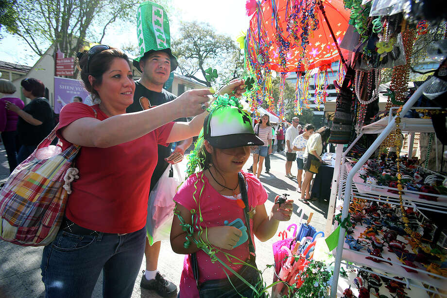 Angela Rios puts a shamrock hat decoration on her daughter Alexzandrea while Carlos Rodriguez watches as St. Patrick's Day is celebrated on the Riverwalk and La Villita  on  March 16, 2013. Photo: TOM REEL, Express-News
