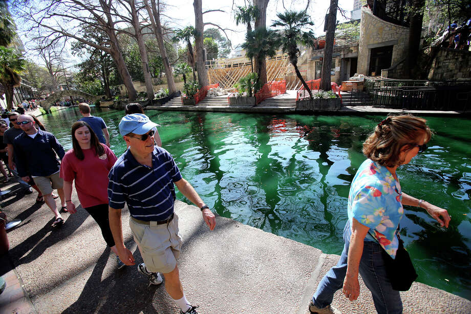 Tourists walk along a green river as St. Patrick's Day is celebrated on the Riverwalk and La Villita  on  March 16, 2013. Photo: TOM REEL, Express-News