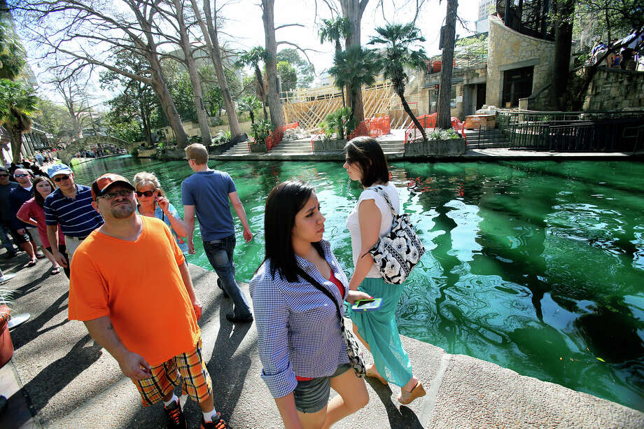 Tourists walk along a river dyed green as St. Patrick's Day is celebrated on the Riverwalk and La Villita  on  March 16, 2013. Photo: TOM REEL, Express-News