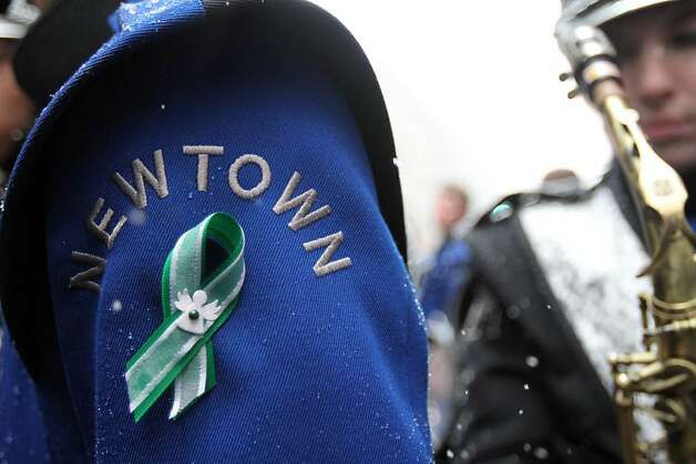 A green and white ribbon, the colors of Sandy Hook Elememtary School in Newtown, Conn., is seen on the uniform of a Newtown High School Marching Band member after marching in the St. Patrick's Day Parade on Saturday March 16, 2013 in New York. The band, from Newtown, Conn., wore the ribbons in remembrance of the victims of the shooting at Sandy Hook Elementary School. (AP Photo/Tina Fineberg) Photo: Tina Fineberg, Associated Press