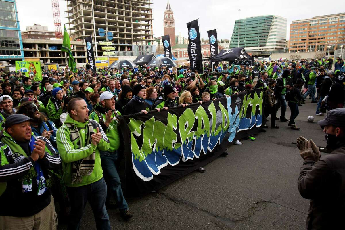Seattle Sounders fans chant and wave flares in a show of friendly intimidation during the pre-game rally and march to stadium before a game against the Portland Timbers Saturday, March 16, 2013, at CenturyLink Field in Seattle.