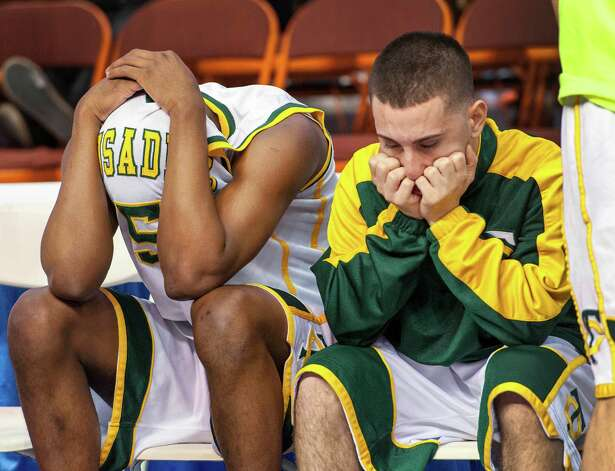 Trinity Catholic High School's Brandon Wheeler and a teammate sit on the bench dejected after losing to Woodstock Academy in the CIAC class L boys basketball championship game at Mohegan Sun Arena in Uncasville, Conn. on Saturday, March 16, 2013. Photo: Mark Conrad / Connecticut Post Freelance