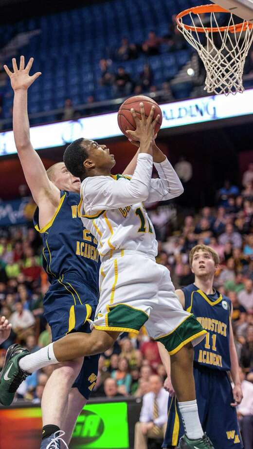 Trinity Catholic High School's Tyrell St. John gets airborne for a shot in the CIAC class L boys basketball championship game against Woodstock Academy at Mohegan Sun Arena in Uncasville, Conn. on Saturday, March 16, 2013. Photo: Mark Conrad / Connecticut Post Freelance