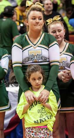 A Trinity Catholic High School cheerleader and fan stand dejected after the loss to Woodstock Academy in the CIAC class L boys basketball championship game at Mohegan Sun Arena in Uncasville, Conn. on Saturday, March 16, 2013. Photo: Mark Conrad / Connecticut Post Freelance