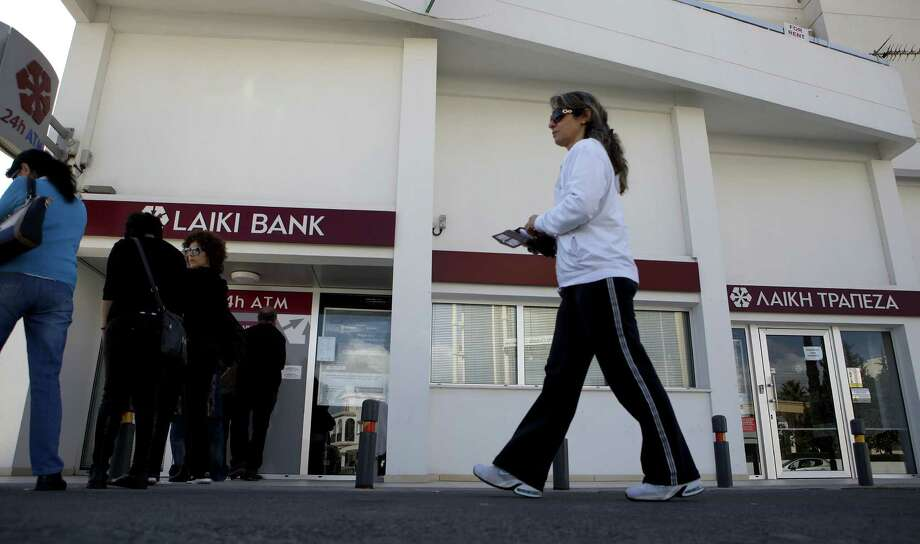 People rush to use ATMs outside of a Laiki Bank branch in Larnaca, Cyprus, after they learned of the bailout agreement. Photo: Petros Karadjias / Associated Press