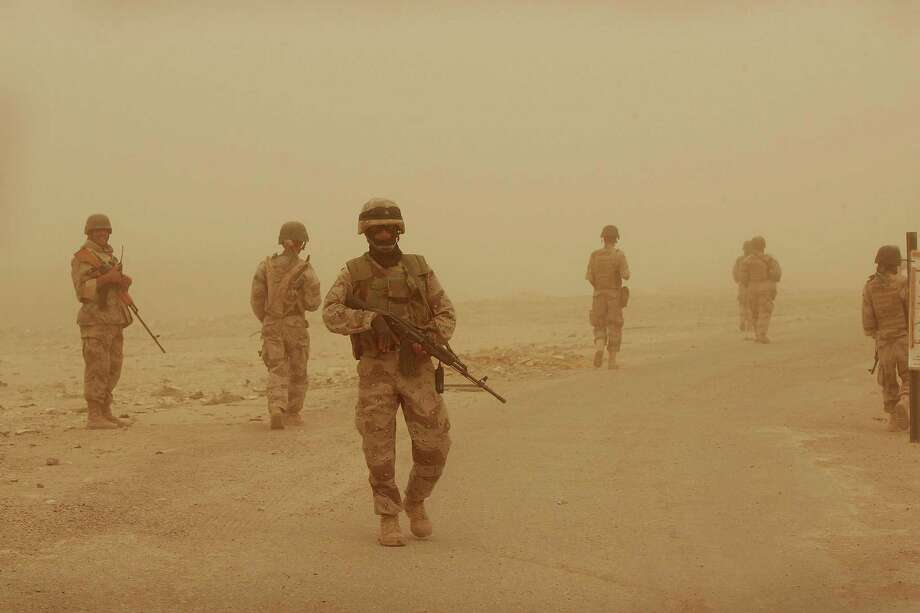 Soldiers from the 2nd Battalion of the Iraqi Ground Forces patrol during a sandstorm in 2005 in Fallujah. This month marks 10 years since the start of the Iraq War. Photo: Scott Olson, Staff / 2005 Getty Images