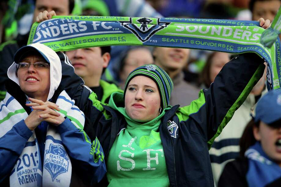 Fans of the Seattle Sounders hold up their iconic green and blue scarves during the first half of a game Saturday, March 16, 2013, at CenturyLink Field in Seattle. Photo: JORDAN STEAD / SEATTLEPI.COM