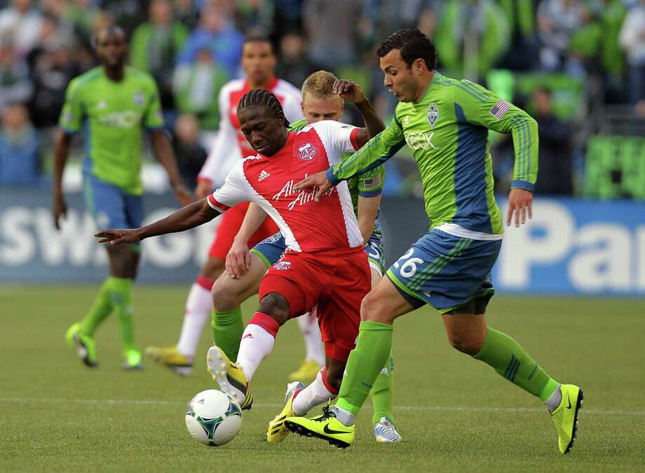 Sounders forward Samuel Ochoa, right, attempts to steal the ball away from Diego Chara, center, of the Portland Timbers,  during the first half of a game Saturday, March 16, 2013, at CenturyLink Field in Seattle. Photo: JORDAN STEAD / SEATTLEPI.COM