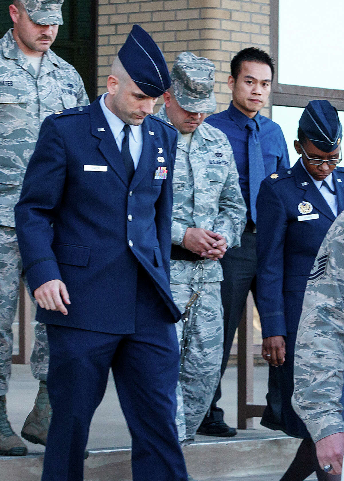 A shackled Staff Sgt. Eddy Soto (center) is escorted out of a building at Joint Base San Antonio-Lackland after being found guilty.
