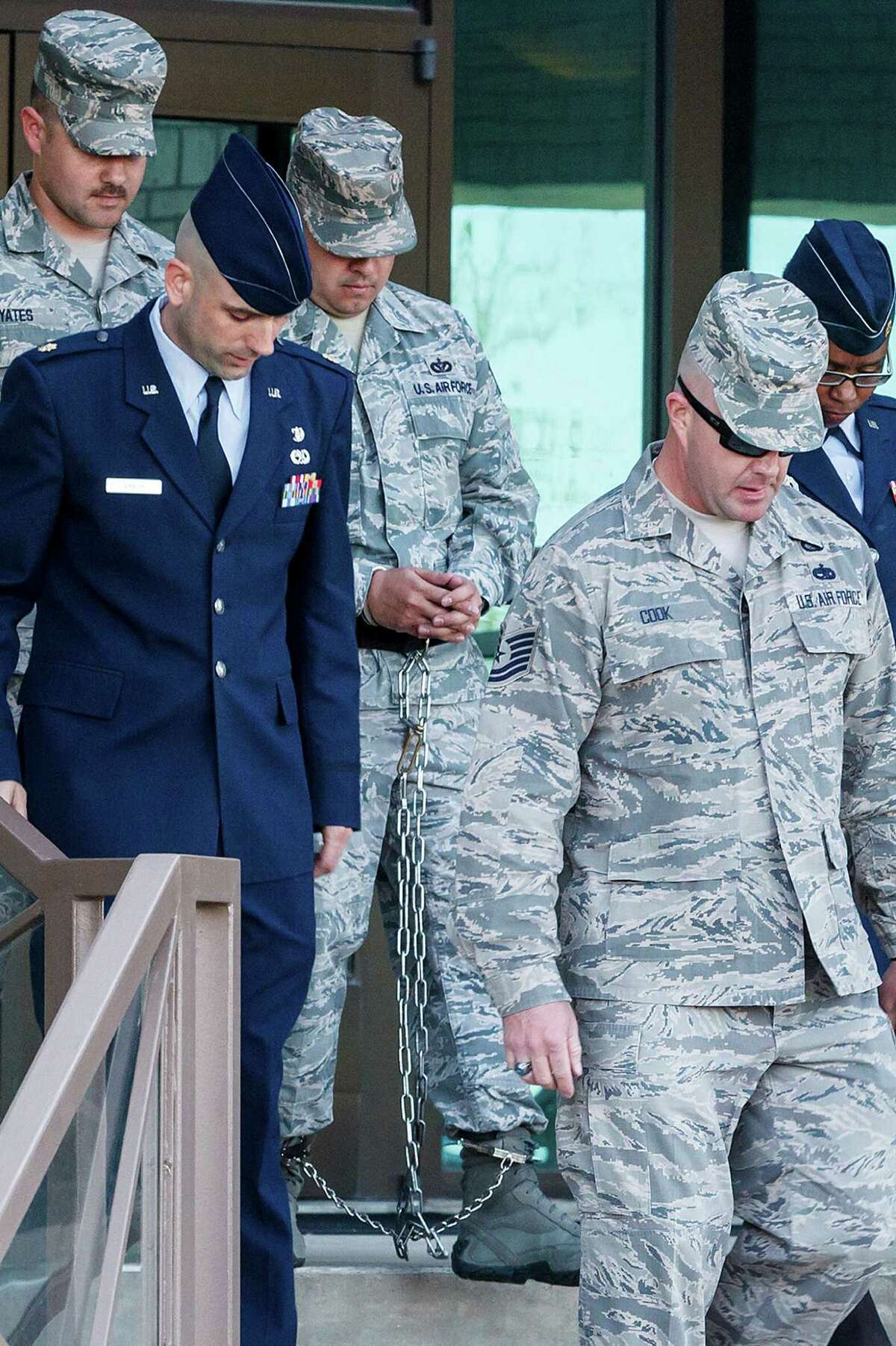 """A shackled Staff Sgt. Eddy Soto (center) is escorted out of the 37th Training Wing headquarters building at Lackland after his Article 32 hearing on Saturday, March 16, 2013. Soto is the second basic training instructor to be found guilty of rape. He was also accused of having an """"unprofessional relationship"""" with a female trainee and of sexually assaulting two female former trainees."""