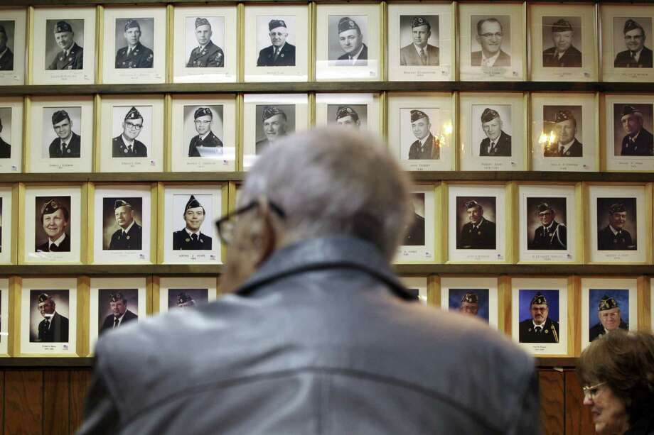 Portraits of past commanders line a wall at American Legion Post 57 in Elgin, Ill., where membership is down dramatically. Photo: Sally Ryan / New York Times