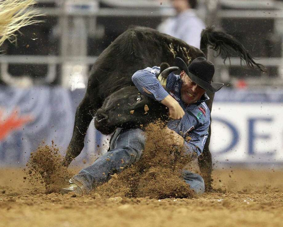 K.C. Jones wrestles a steer to win the Steer Wrestling competition during the final BP Super Series Championship at the Houston Livestock Show and Rodeo Saturday, March 16, 2013, in Houston. Photo: Karen Warren, Houston Chronicle / © 2013 Houston Chronicle
