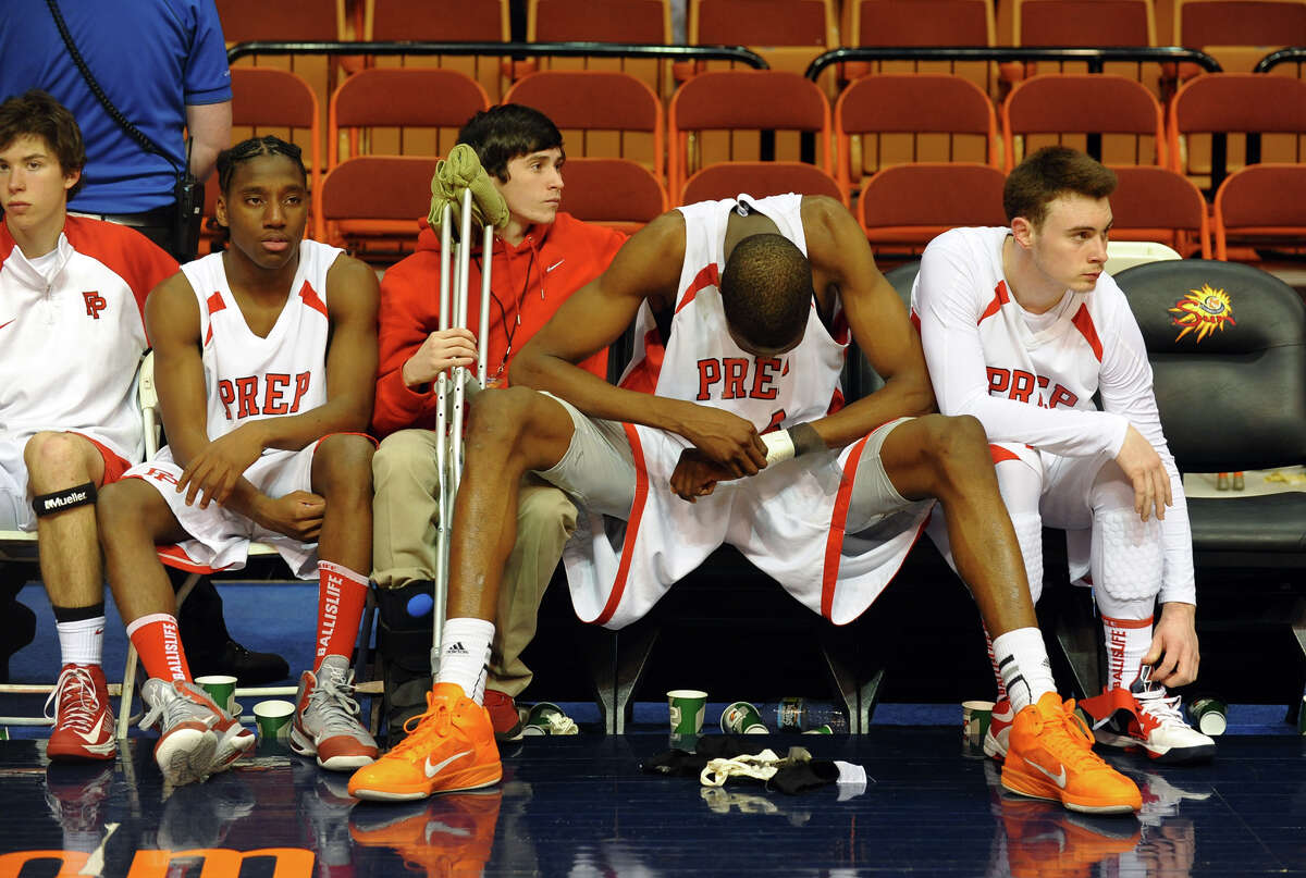 Fairfield Prep's #44 Paschal Chukwu, second from right, sits dejected with the rest of the team on the bench after being defeated by Hillhouse in Class LL boys basketball final action in Uncasville, Conn. on Saturday March 16, 2013.