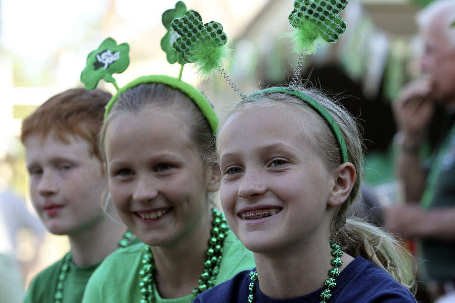 Shannon Breuer (right) and siblings Molly and Colin watch the goings-on at the Beethoven Maennerchor. In America, St. Patrick's Day began in the 1700s as a religious celebration by Irish immigrants, said Carolyn Dowd of the Harp & Shamrock Society of Texas. Photo: Tom Reel / San Antonio Express-News