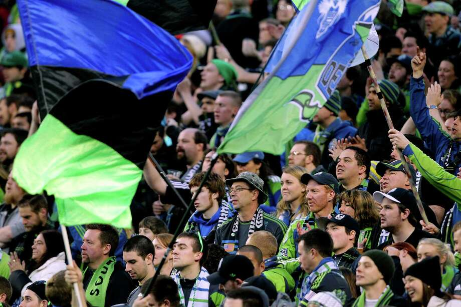 Sounders fans - many dressed in the iconic blue and green color scheme - wave flags and chant for their home team during second half of a game against the Portland Timbers Saturday, March 16, 2013, at CenturyLink Field in Seattle. Photo: JORDAN STEAD / SEATTLEPI.COM