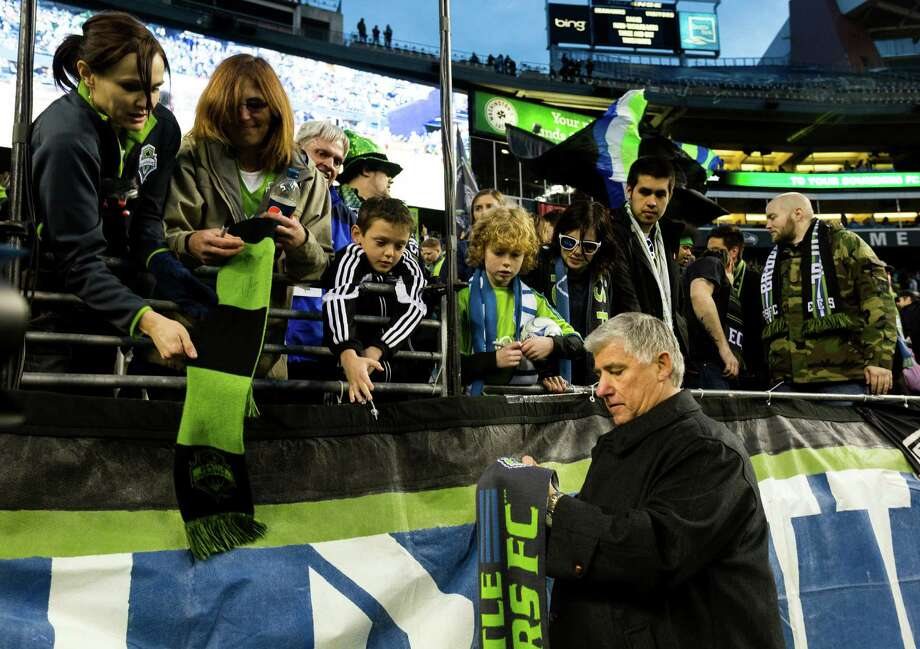 Sounders head coach Siegfried Schmid, right, signs scarves for fans following the second half of a game against the Portland Timbers Saturday, March 16, 2013, at CenturyLink Field in Seattle. The Seattle Sounders and the Portland Timbers tied with a final score of 1-1. Photo: JORDAN STEAD / SEATTLEPI.COM