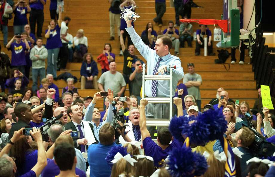 Albany coach Will Brown, top, holds up the in celebration after they defeated Vermont 53-49 in an NCAA college basketball game in the championship of the America East Conference tournament in Burlington, Vt. on Saturday, March 16, 2013. (AP Photo/The Burlington Free Press, Glenn Russell) NO SALES Photo: Glenn Russell