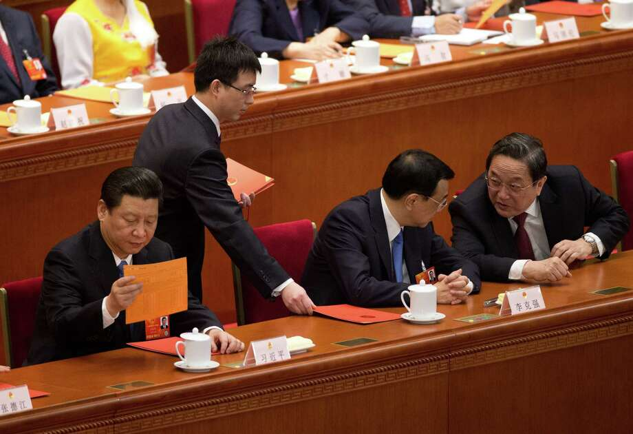 Chinese President Xi Jinping, left, looks at a ballot distribute by an officer while Premier Li Kiqiang, center, chats with Chinese People's Political Consultative Conference chairman Yu Zhengsheng, right, during a plenary session of the National People's Congress at the Great Hall of the People in Beijing Saturday, March 16, 2013. China's new leaders turned Saturday to veteran technocrats with greater international experience to staff a Cabinet charged with overhauling a slowing economy and pursuing a higher global profile for the country without triggering opposition. (AP Photo/Andy Wong) Photo: Andy Wong