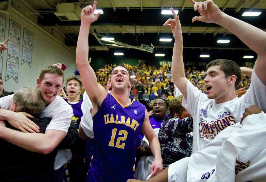 Albany's Peter Hooley (12) celebrates with teammates after their 53-49 victory over Vermont in an NCAA college basketball game in the championship of the America East Conference tournament in Burlington, Vt. on Saturday, March 16, 2013. (AP Photo/The Burlington Free Press, Glenn Russell) NO SALES Photo: Glenn Russell