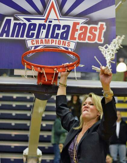 UAlbany head coach Katie Abrahamson-Henderson cuts down the net after defeating Hartford for the Ame